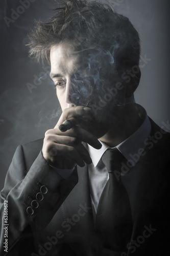 Young stylish man smoking a cigar
