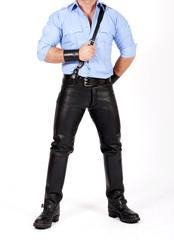 Mann in Lederhosen,Stiefeln und blauem Hemd