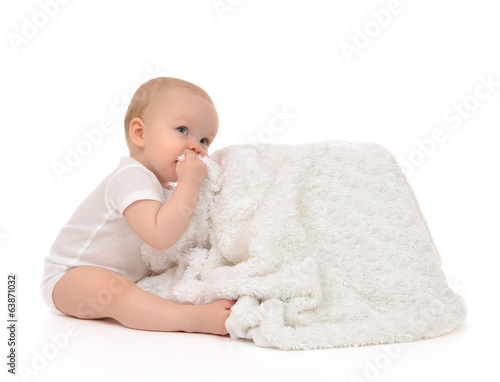 Infant child baby toddler sitting and eating soft blanket towel