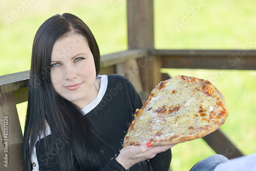 Young happy woman eating pizza