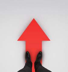 businessman standing on red arrow