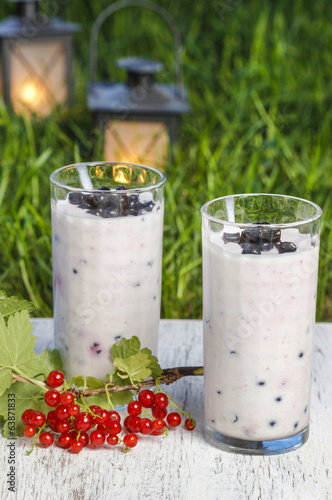 Blueberry and redcurrant smoothie on wooden tray. Garden party,