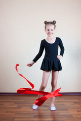 Girl gymnast with red ribbon
