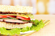 Fresh and tasty sandwich on plate on table on light background