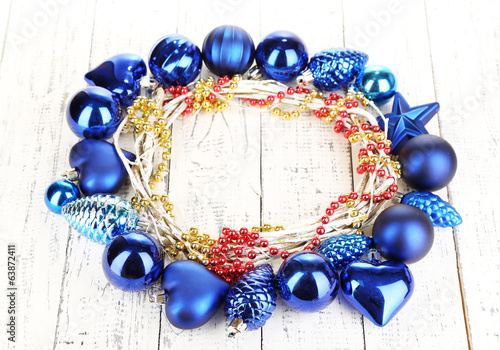 Christmas wreath of colorful balls on wooden table close-up