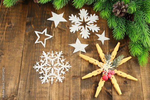 Beautiful snowflakes with fir branch on wooden background
