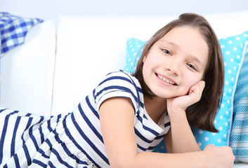 Beautiful little girl lying on sofa, on home interior