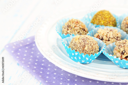 Set of chocolate candies, on plate, on wooden background