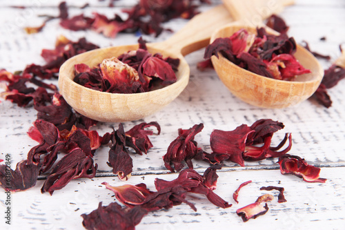 Aromatic dry tea in spoons on wooden background