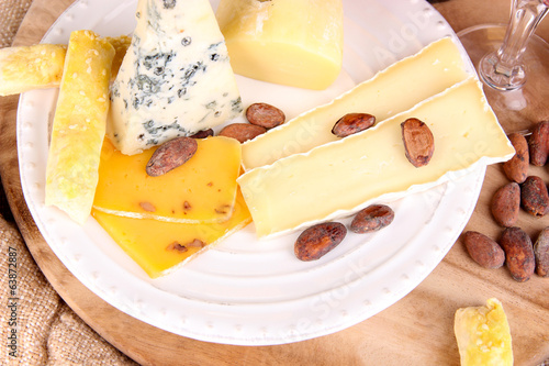 Assorted cheese plate and wine glass on table background