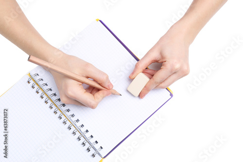 Human hands with pencil and erase rubber and notebook, isolated