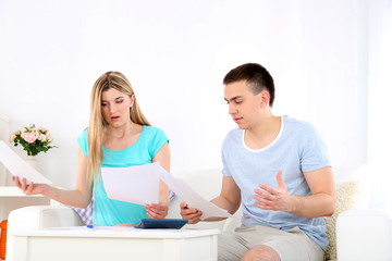 Young couple calculating finance at desk,