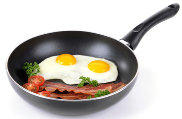 Scrambled eggs and bacon on frying pan isolated on white