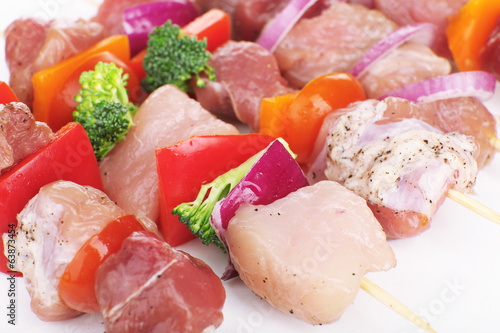 Raw pork kebab with vegetables close up