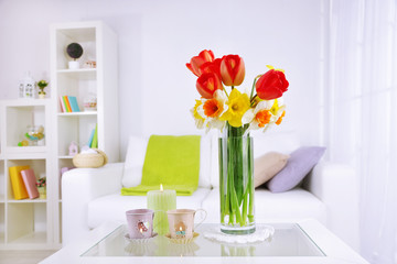 Beautiful spring flowers in vase on home interior background