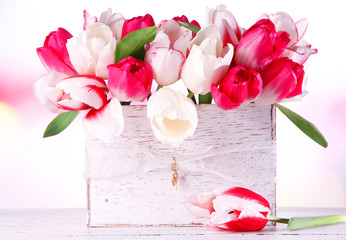 Beautiful tulips  in wooden box, on light background