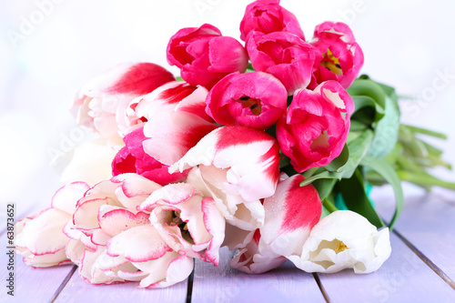 Beautiful tulips on color wooden table, on light background