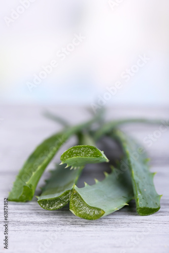 Fresh green aloe leaves on wooden table