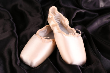 Ballet pointe shoes on black fabric background