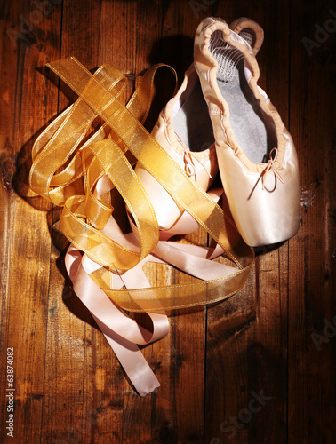 Ballet pointe shoes on wooden background