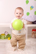 Cute little boy playing with ball in room