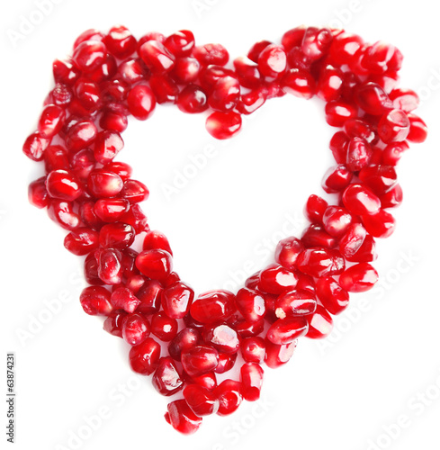 Pomegranate seeds in shape of heart isolated on white