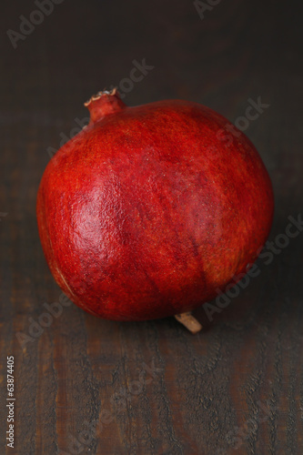 Ripe pomegranate on color wooden background