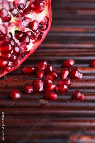 Ripe pomegranate on bamboo mat background