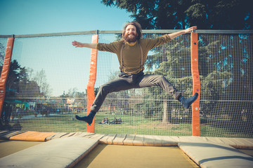 man jumping on trampoline at playground