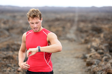 Running athlete man looking at heart rate monitor