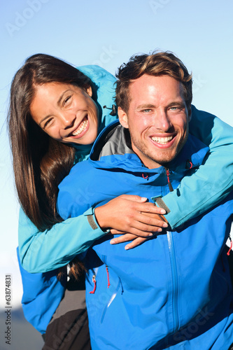 Happy couple piggyback in active lifestyle