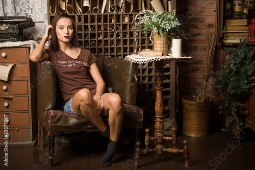 Young woman sits in an armchair