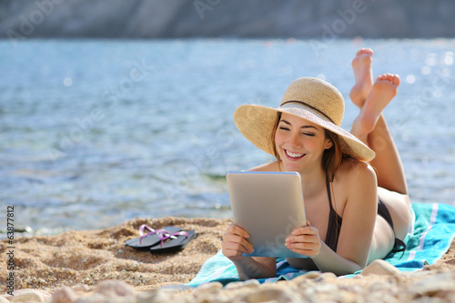 Leinwanddruck Bild Pretty woman reading a tablet reader on the beach on vacations