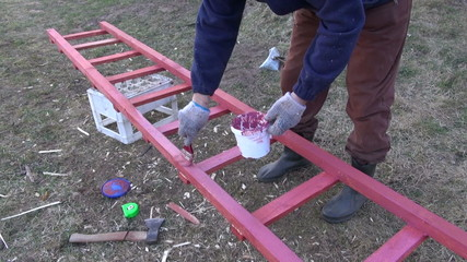 gardener paint in red new wooden ladder