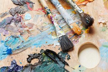 three old paintbrushes on used artistic pallette