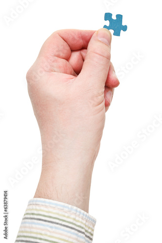 male hand in shirt holding jigsaw puzzle piece