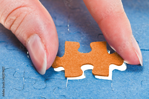 inserting the last orange piece of puzzle