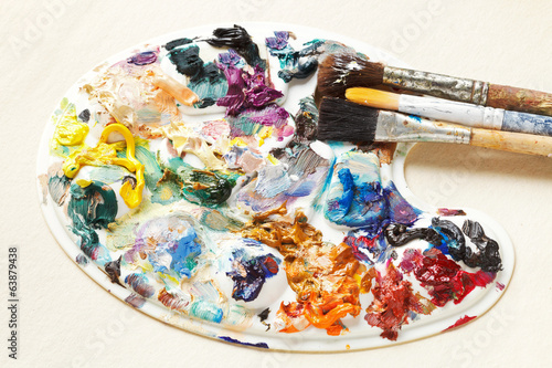 artistic pallette with oil paints and paintbrushes