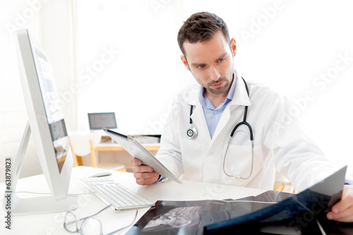 Portrait of a young doctor using tablet at work