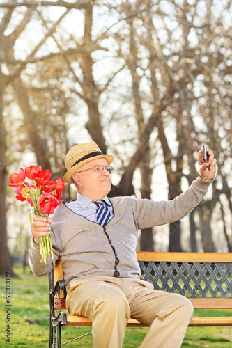 Elderly holding tulips and taking selfie in park