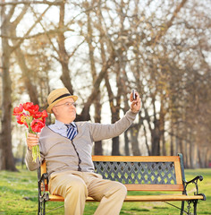Senior holding flowers and taking selfie in park