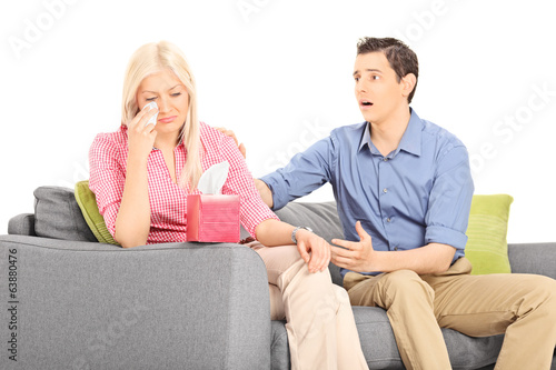 Woman crying seated on sofa with her boyfriend