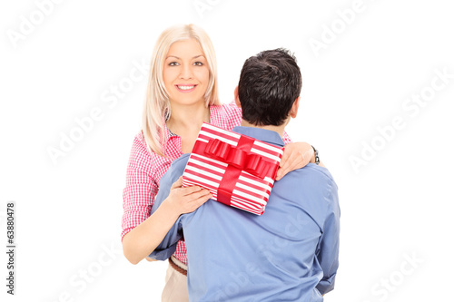 Woman hugging a man and holding a present