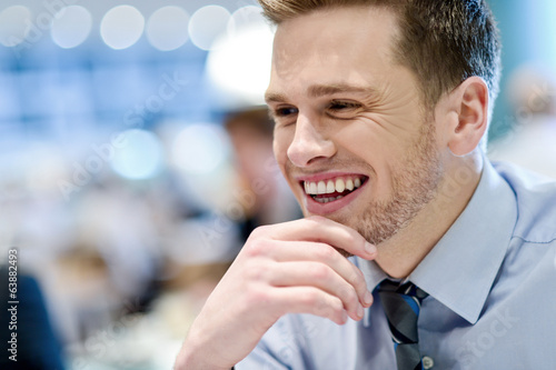 Smiling young man sitting in a outdoor cafe