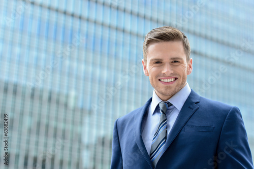 Smart young businessman looking at camera