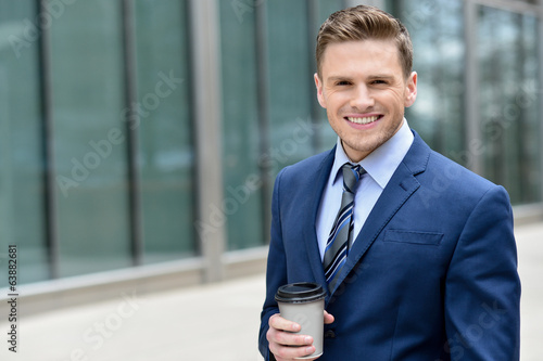 Smiling businessman with coffee sipper