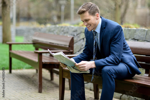 Smiling businessman reading newspapers in park