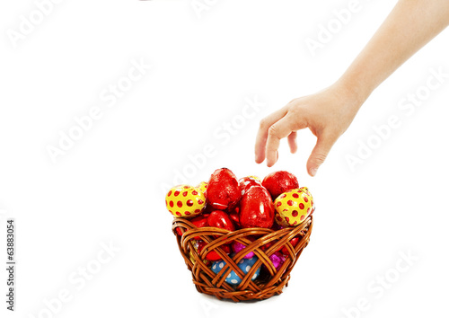 Child's hand takes the eggs from the basket