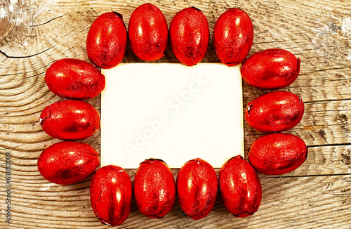 Chocolate Easter eggs wrapped in foil on wooden background