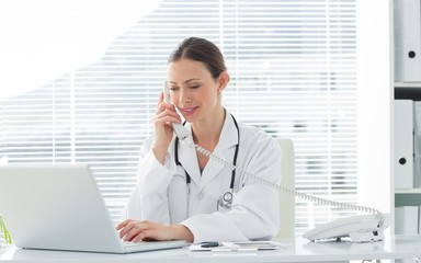 Doctor using land line phone and laptop